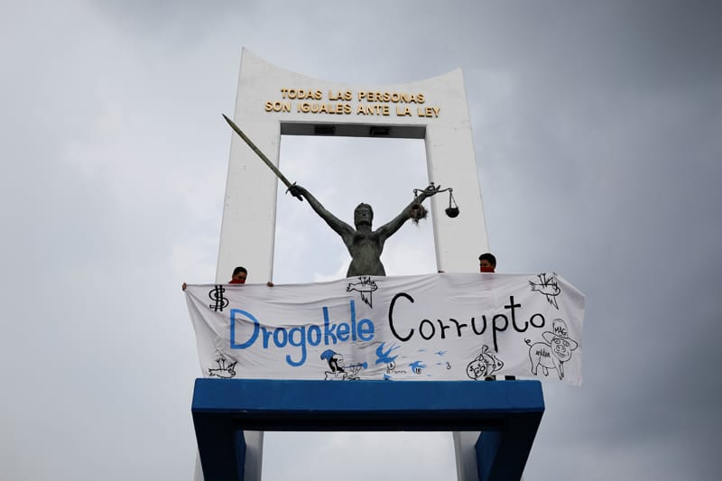 People hold a banner next to a monument in San Salvador, El Salvador, May 2, 2021, as they protest the Salvadoran congress' removal of constitutional court judges and the attorney general. (CNS photo/Jose Cabezas, Reuters)