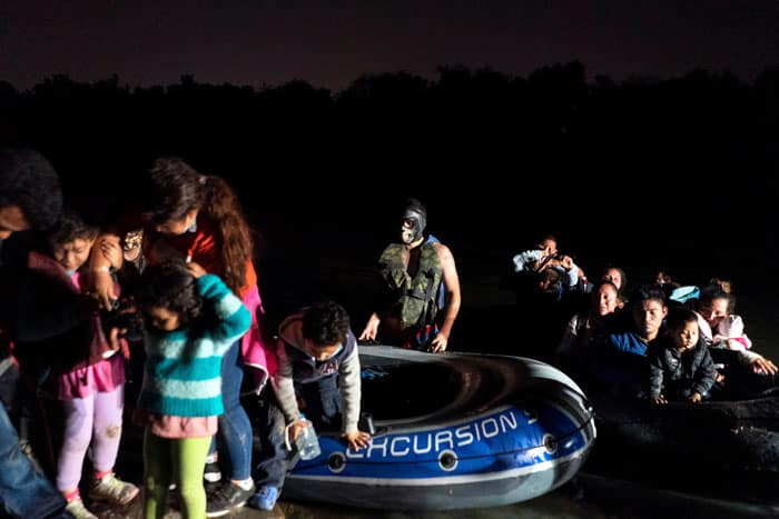 Asylum-seeking migrant families disembark from an inflatable raft in Roma, Texas, after crossing the Rio Grande April 7, 2021. (CNS photo/Go Nakamura, Reuters)