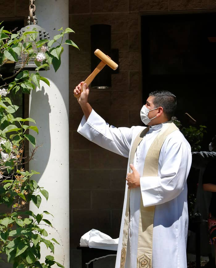 stop AAPI hate- Father Manuel Dorantes, pastor of St. Mary of the Lake in Chicago, rings a bell at the Buddhist Temple of Chicago May 2, 2021, during an interfaith rally against racism toward Asian Americans and Pacific Islanders. (CNS photo/Karen Callaway, Chicago Catholic)