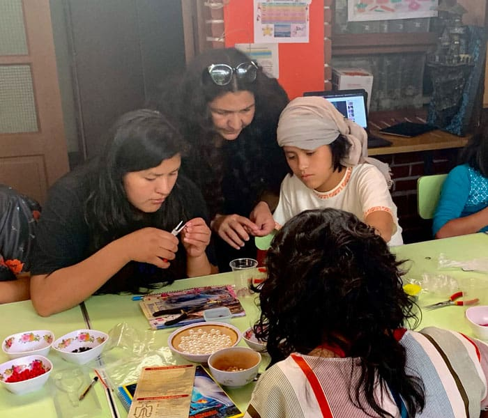 Lorena Simons (center) teaches girls at Our Home shelter in Cochabamba, Bolivia, to make rosaries. (Matthew Sim/Bolivia)