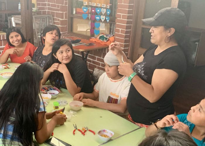 Rossy Bedoya (with black hat) visits girls at Our Home shelter who were victims of abuse and teaches them how to make rosaries. (Matthew Sim/Bolivia)