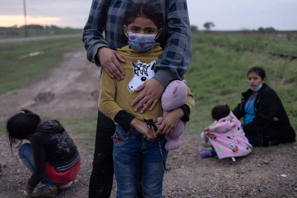 A migrant family from Honduras seeking asylum in the U.S. waits to be transported to a Border Patrol processing facility after crossing the Rio Grande into La Joya, Texas, May 13, 2021. (CNS photo/Adrees Latif, Reuters)