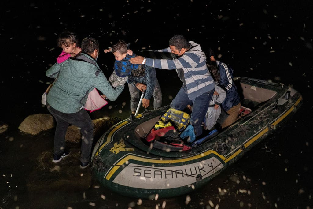 Asylum-seeking families in Roma, Texas, disembark an inflatable raft May 4, 2021, after crossing the Rio Grande from Mexico. (CNS photo/Go Nakamura, Reuters)