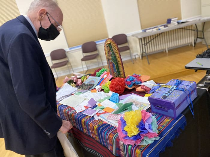 Bishop Guido Charbonneau of Honduras looks at notes written by children in detention camps during a break June 1, 2021, at Mundelein Seminary outside of Chicago. Along with other bishops from Central America and Mexico, he was participating in an emergency meeting June 1, 2 at the urging of U.S. bishops to address immigration. (CNS photo/Rhina Guidos)