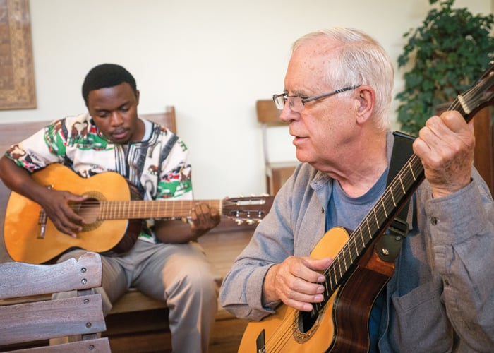 Seminarian Joshua Mutende and Maryknoll Father Paul Masson, spiritual guide for Maryknoll candidates in Bolivia, play guitar during Mass at Maryknoll chapel in Cochabamba. (Nile Sprague/Bolivia)