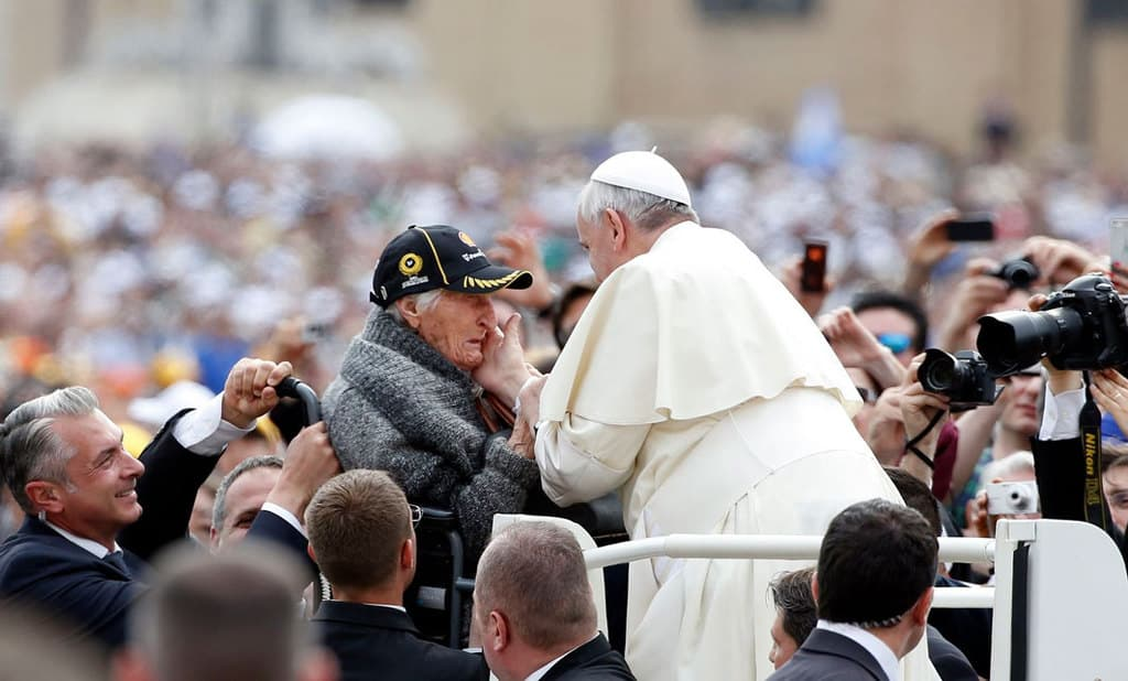 """An elderly woman becomes emotional as Pope Francis greets her as he arrives for a May 2014 weekly audience in St. Peter's Square at the Vatican. Pope Francis wanted the first World Day for Grandparents and the Elderly on July 25 to be inaugurated as the world seeks to recover from a deadly pandemic, calling for the faithful to be """"angels,"""" who care, console and caress. (CNS photo/Tony Gentile, Reuters)"""