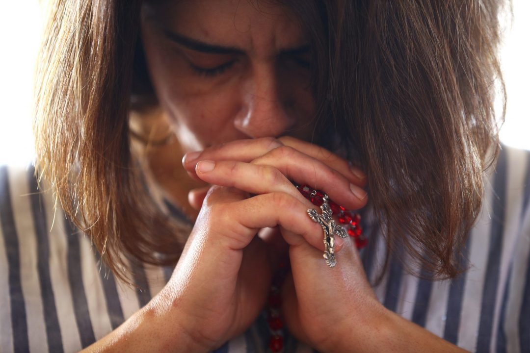 A woman holding a rosary prays during Mass at a church in Beirut Aug. 9, 2020. Lebanon's Christian advocates are urging that a special fund be established to address the continual flow of Christian emigration and to give them a solid reason to remain in their ancestral homeland. (CNS photo/Hannah McKay, Reuters)