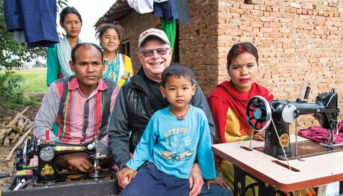 Father Thaler is flanked by Sitaram and Reena Tharu, graduates of the Sewing Cutting Training for Differently Abled Persons, as he visits their home. Trainees of the couple stand behind while a young neighbor sits with the Maryknoll priest. (Gregg Brekke/Nepal)