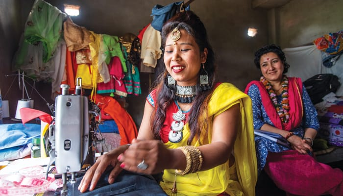 Samjhana Tharu, a graduate of the Sewing Cutting Training Program for Deprived Women in the Bardiya District of Nepal, sews as Shailee Singh Rahour, project director for the Maryknoll Fathers and Brothers in Nepal, proudly looks on. (Gregg Brekke/Nepal)