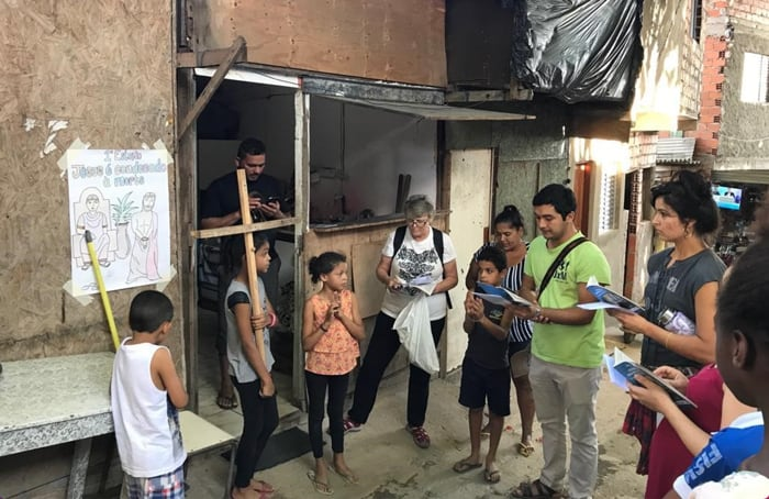Margarita Durán (right) joins Holy Rosary Sister Ann Griffin (white shirt), Spiritan Seminarian Oscar Britez and community members at outdoor Stations of the Cross. (Anastasia Lee/Brazil)