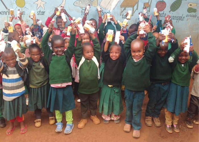 Students at St. Paul Academy who could not afford uniforms and backpacks received them along with snacks for all from Hope on Hooves. (Courtesy of Samson Gladstone/Tanzania)