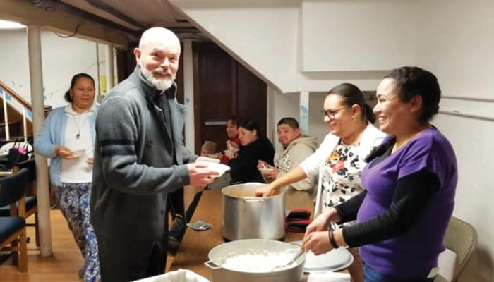 Father Lopez-Cardinale, pastor of St. Benedict Church, enjoys a meal with community members at a parish event in 2019. (Courtesy of Alejandro Lopez-Cardinale/U.S.)
