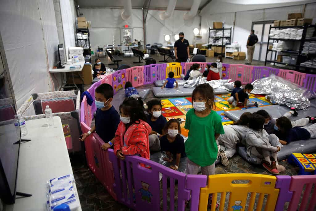 Young unaccompanied migrants, ages 3 to 9, watch television inside a playpen March 30, 2021, at the holding facility in Donna, Texas, set up in February by U.S. Customs and Border Protection, an agency within the Department of Homeland Security. (CNS photo/Dario Lopez-Mills, Pool via Reuters)