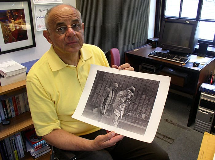In this file image, Maryknoll Father Raymond Nobiletti holds a photo taken by Gulnara Samoilova on Sept. 11, 2001, after the south tower of the WTC collapsed, covering the priest, who was ministering to burn victims, and everyone nearby in a dark cloud of ashes. (Schwartz/U.S.)