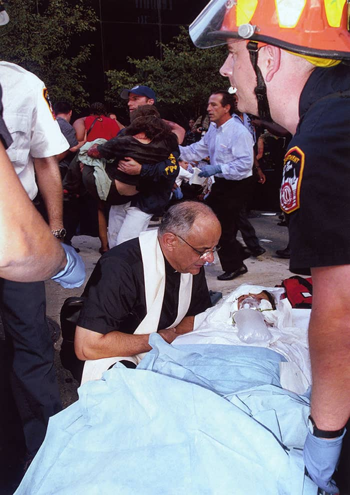 On Sept. 11, 2001, Richard Cohen took this photo of Maryknoll Father Raymond Nobiletti anointing and praaying over Elaine Duch, who worked on the 88th floor of the World Trade Center's north tower, where the first plane hit.